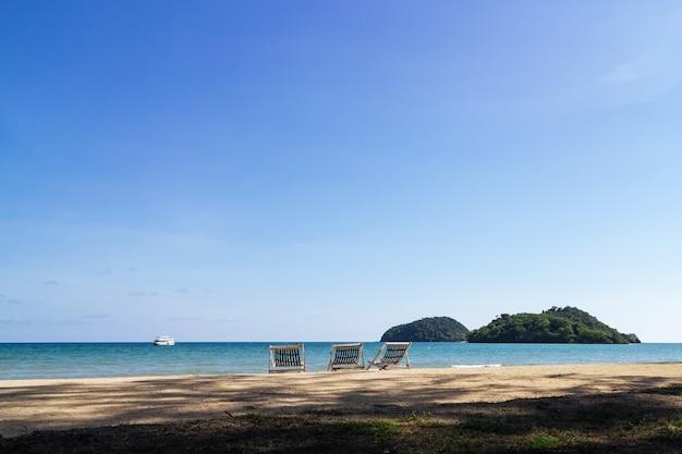 Trzy składane krzesła plażowe na plaży z morza i jasne niebo w tle.