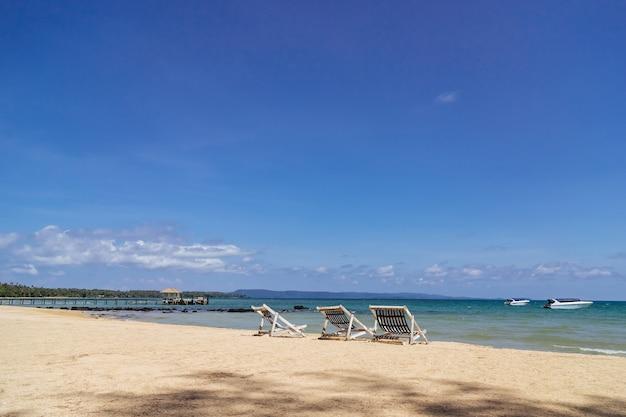 Trzy składane krzesła plażowe na plaży z morzem i jasne niebo w tle w koh mak w trat