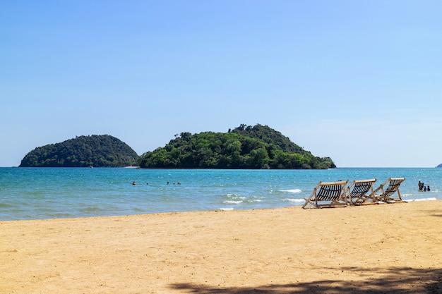Trzy składane krzesła plażowe na plaży z morzem, jasne niebo