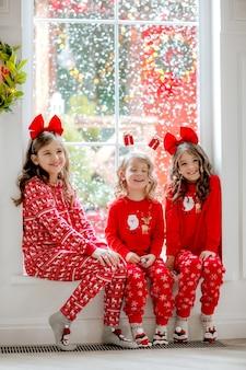 Trzy śliczne dziewczyny w czerwonych świątecznych piżamach i opaskach na głowie siedzą przy dużym oknie, a na zewnątrz pada śnieg.