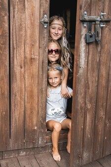 Trzy śliczne małe siostry dziewczynki bawiące się razem w drewnianej stodole