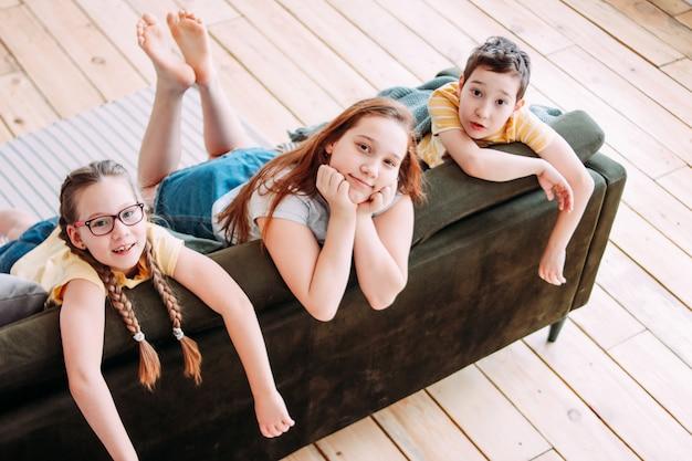 Trzy ślicznego uśmiechniętego dziecko przyjaciela tweens siedzi na kanapie w domu