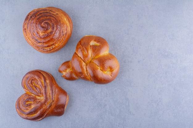 Trzy słodkie bułeczki ułożone na marmurowej powierzchni