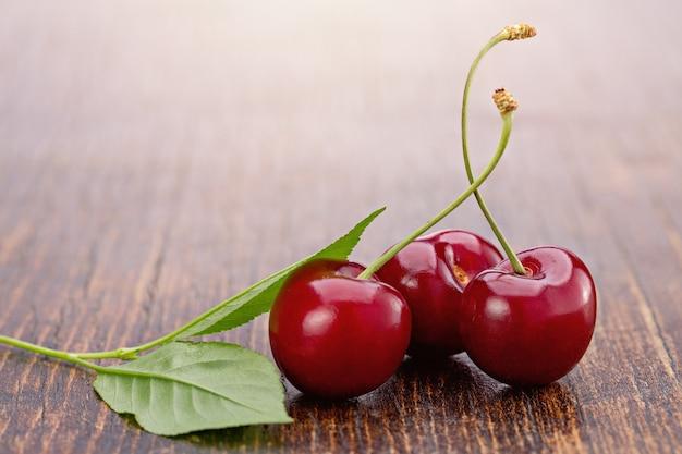 Trzy słodkie czerwone jagody wiśni z zielonymi liśćmi na brązowym drewnianym stole studio strzał kopia przestrzeń