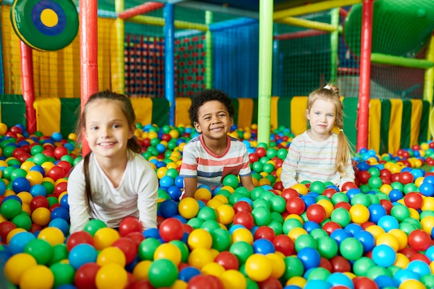 Trzy słodkie dzieci bawiące się w ballpit