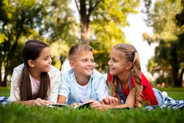 Trzy słodkie dzieci leżące na kocu
