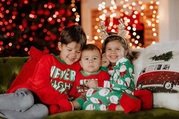 Trzy słodkie małe dzieci w świątecznej piżamie, pozowanie na zielonej kanapie przed świątecznym otoczeniem