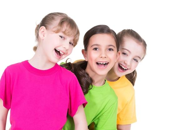 Trzy słodkie małe słodkie uśmiechnięte dziewczyny w kolorowych koszulkach stoją za sobą na białym tle.