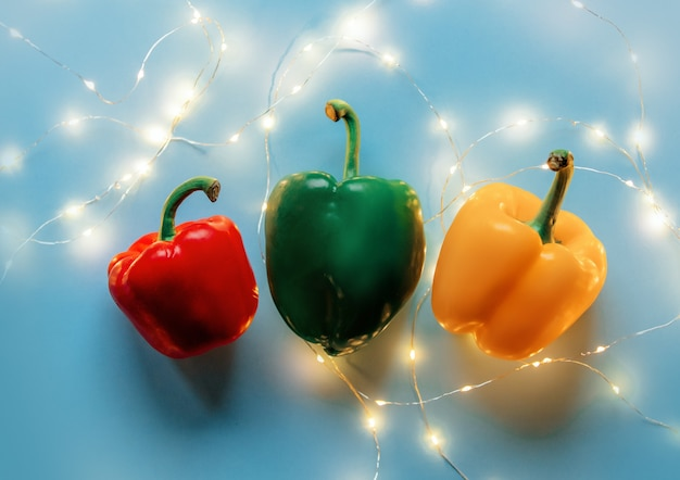Trzy słodkie papryki, czerwone, zielone i żółte z bajkowymi światłami na niebieskim tle