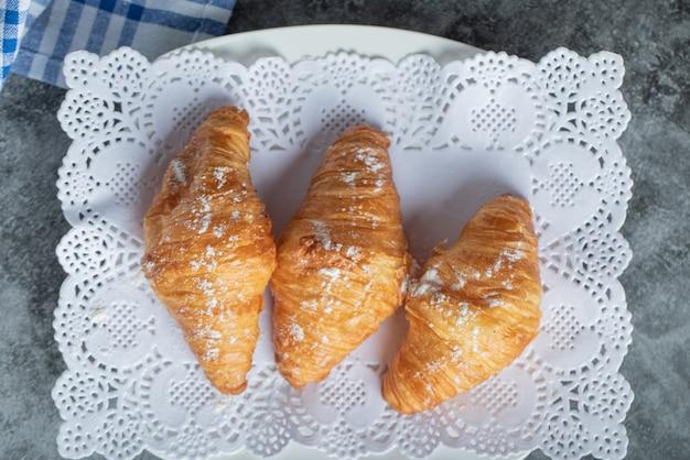 Trzy słodkie rogaliki z cukrem pudrem na białej serwetce.