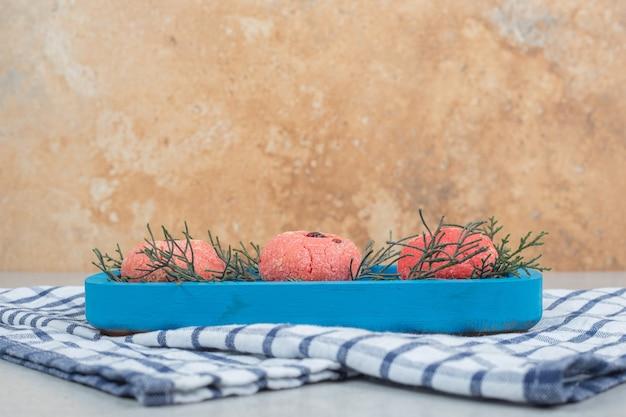 Trzy słodkie różowe okrągłe ciasteczka na niebieskim talerzu