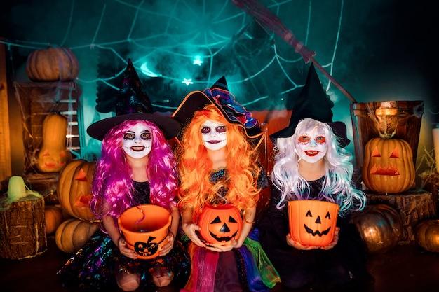 Trzy słodkie śmieszne siostry obchodzą święto. wesołe dzieci w strojach karnawałowych gotowe na halloween.