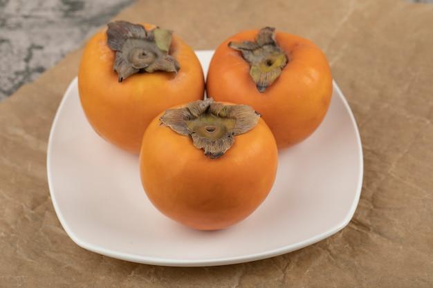 Trzy smaczne persimmon fuyu na białym talerzu na marmurowej powierzchni