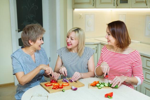 Trzy śmieszne kobiety kroją sałatkę w kuchni