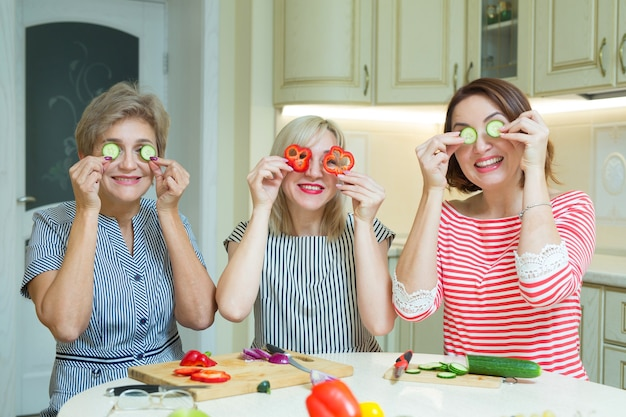 Trzy śmieszne kobiety krojenia warzyw w dłoniach w kuchni