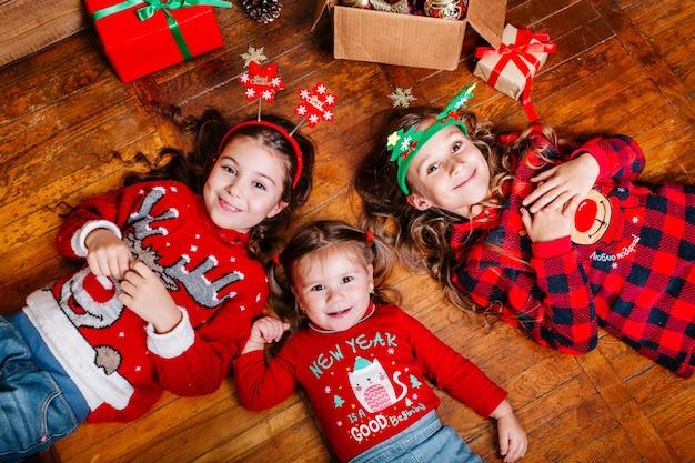 Trzy śmieszne małe siostry leżą na podłodze w domu
