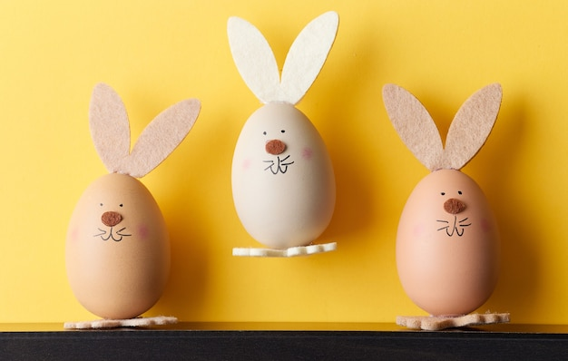 Trzy śmieszne pisanki w kształcie króliczka na żółtym tle