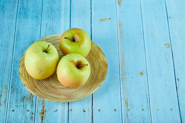 Trzy soczyste jabłka na talerzu ceramicznym i niebieskim stole.