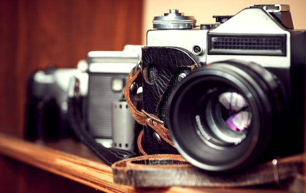 Trzy stare zabytkowe kamery na drewnianej półce