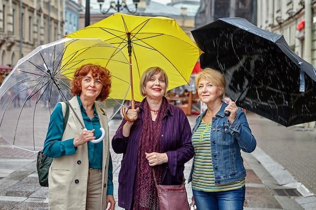 Trzy starsze kobiety rasy kaukaskiej stoją pod parasolami na ulicy europejskiego miasta w deszczową pogodę.