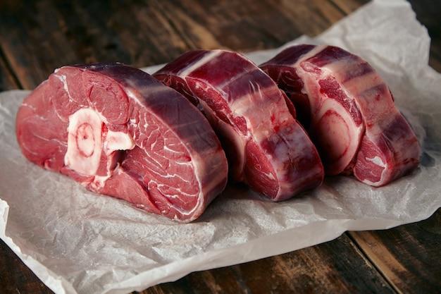 Trzy steki ze świeżego mięsa na drewnianym stole z białego papieru rzemieślniczego