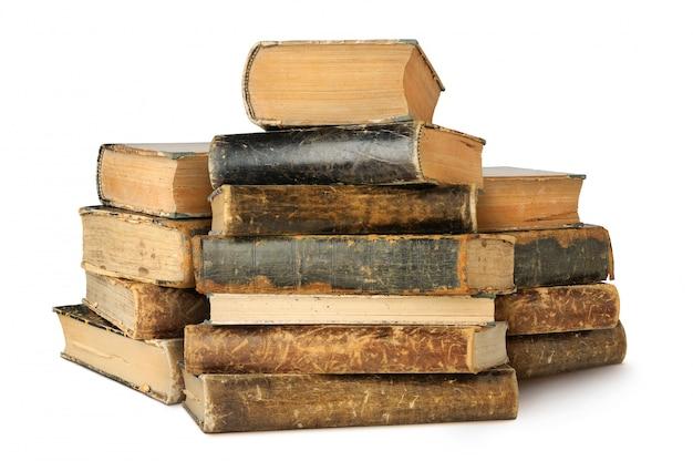 Trzy stosy starych książek na białym tle