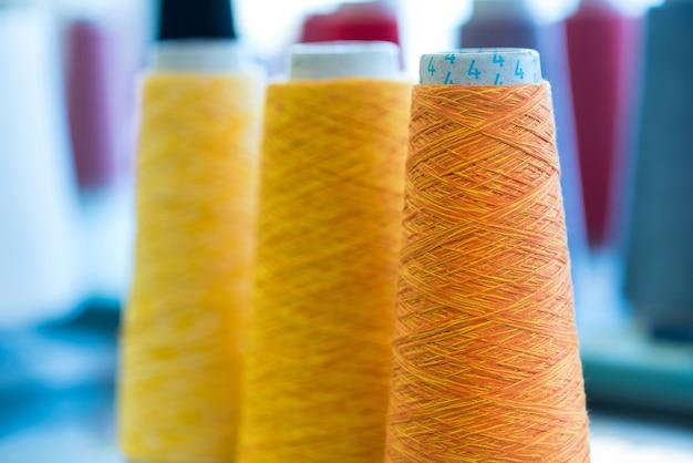 Trzy stożkowe szpule kolorowej żółtej i pomarańczowej nici kaszmirowej w fabryce dzianin z naciskiem na pomarańczową rolkę na pierwszym planie