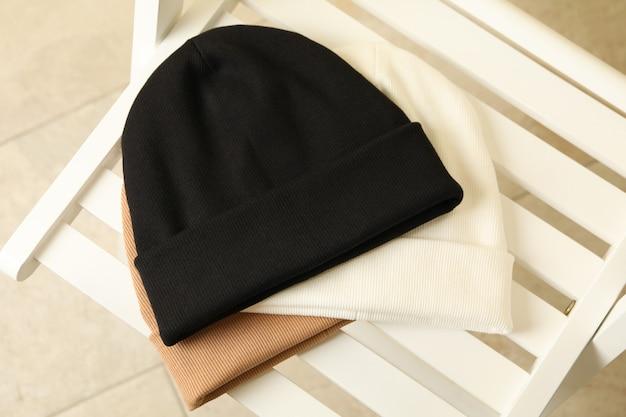 Trzy stylowe czapki na drewnianym krześle