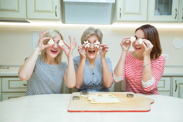 Trzy stylowe dorosłe kobiety robiące ciasteczka w kuchni