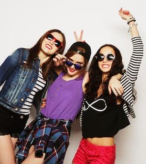 Trzy Stylowe Seksowne Hipster Dziewczyny Najlepsi Przyjaciele. Stojąc Razem I Dobrze Się Bawiąc. Patrząc Na Aparat. Na Szarym Tle. Premium Zdjęcia