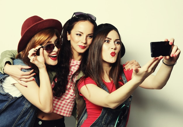 Trzy stylowe seksowne hipsterskie dziewczyny najlepsze przyjaciółki biorące selfie z telefonem komórkowym