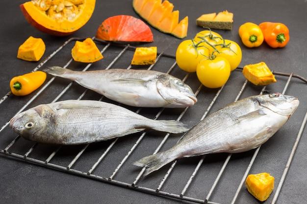 Trzy surowe ryby dorado na grillu.