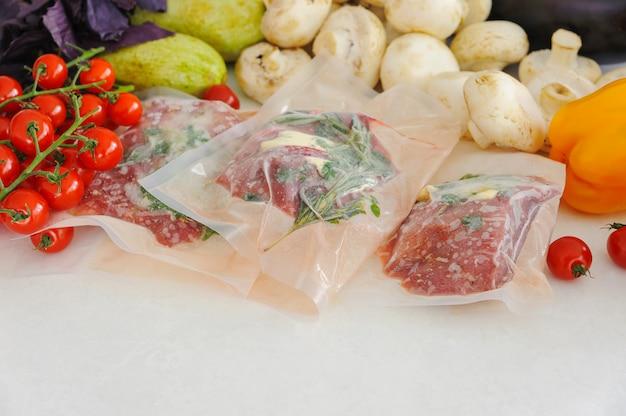 Trzy surowe steki w opakowaniu próżniowym, warzywa i grzyby. kuchnia sous-vide, nowa technologia.