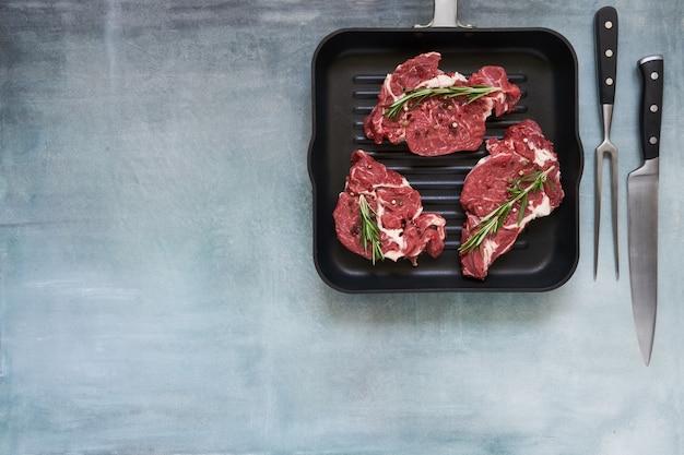 Trzy surowe steki wołowe z rozmarynem i pieprzem na patelni. widok z góry, miejsce na kopię.