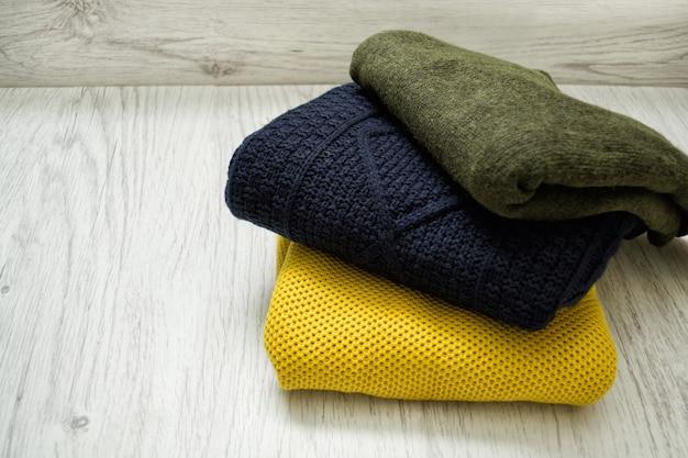 Trzy swetry w ciepłych kolorach na drewnianym tle. modna koncepcja.