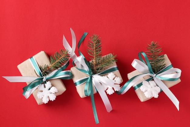 Trzy świąteczne pudełka na prezenty z zieloną i białą wstążką na czerwonej powierzchni