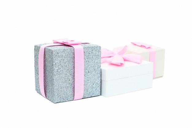 Trzy świąteczne pudełka z prezentami związane z satynową tasiemką na białym tle.