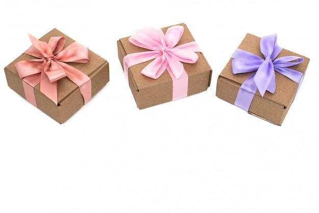 Trzy świąteczne pudełka z prezentami związane z satynową wstążką na białym tle.