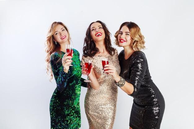Trzy świętujące kobiety w błyszczących wieczorowych strojach cieszą się razem czasem, piją wino i tańczą