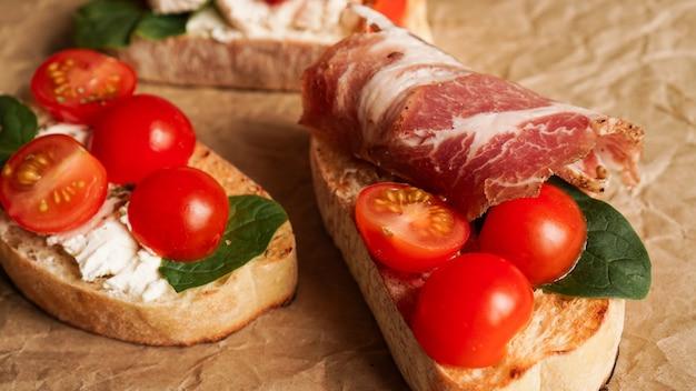 Trzy świeże bruschetta na papierze rzemieślniczym. przystawka z ciabattą, serem, pomidorami, boczkiem i szpinakiem. pyszna przekąska