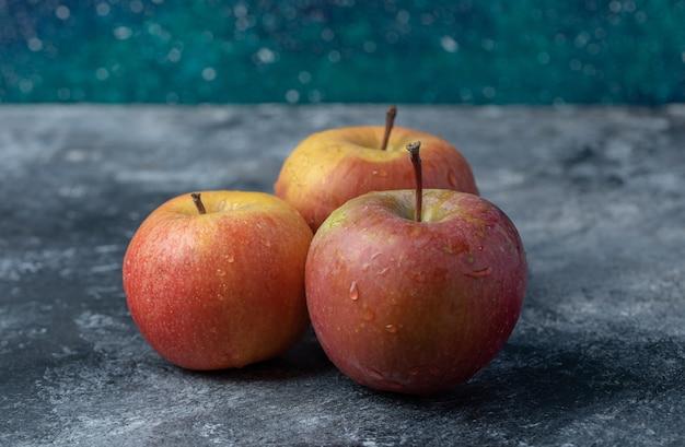 Trzy świeże czerwone jabłka na marmurowym tle.