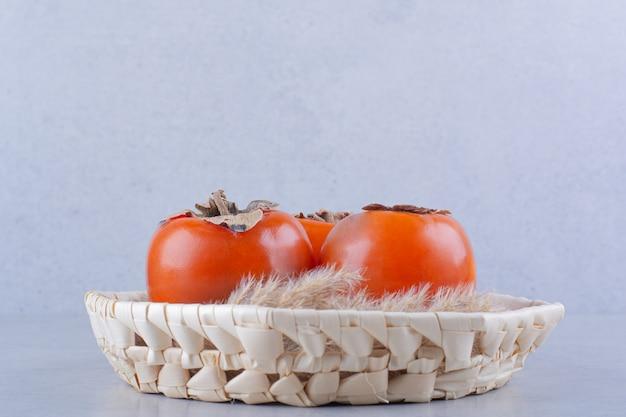 Trzy świeże dojrzałe owoce persimmon w wiklinowym koszu.