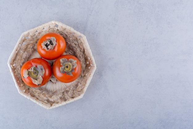 Trzy świeże Dojrzałe Owoce Persimmon W Wiklinowym Koszu. Darmowe Zdjęcia