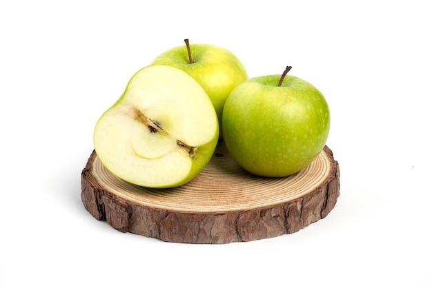 Trzy świeże jabłka całe i pokrojone na drewnianym kawałku.