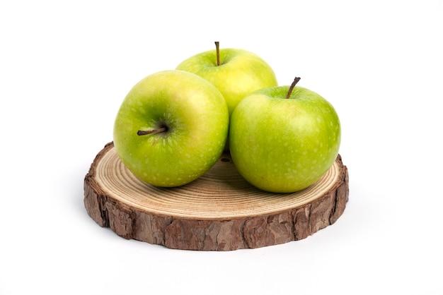 Trzy świeże jabłka na drewnianym kawałku.