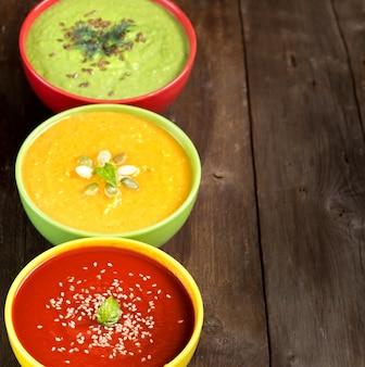 Trzy świeże kolorowe zupy warzywne - pomidor, dynia i zielony groszek na drewnianym stole