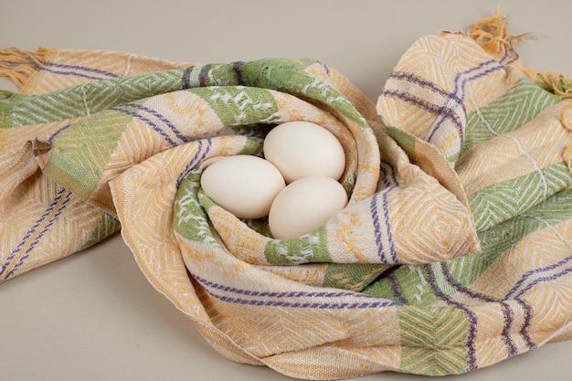 Trzy świeże kurze białe jajka na obrusie.