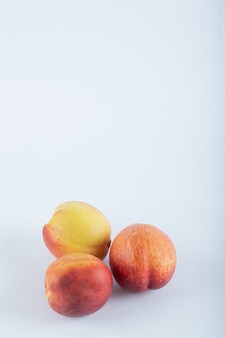 Trzy świeże nektaryny na białym tle.