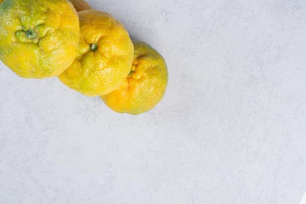 Trzy świeże organiczne mandarynki na szarym tle.