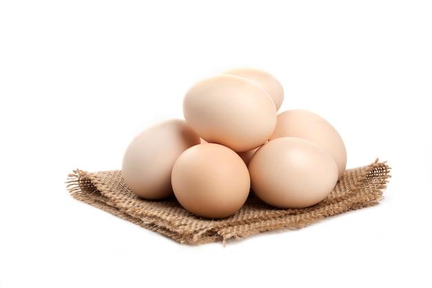 Trzy świeże organiczne surowe jaja na białym tle na białej powierzchni.
